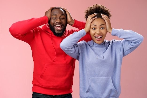 Waist-up happy charming surprised couple african american girlfriend boyfriend winning awesome gift lottery smiling impressed did not except win cannot believe luck grinning holding head shocked