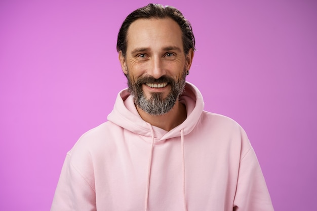 Waist-up happy cheerful caucasian bearded man grey hair in pink trendy hoodie smiling broadly feel healthy attend gym lead active lifestyle grinning white perfect teeth, standing purple background.