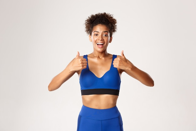 Waist-up of happy and healthy fit woman in blue sport oufit, looking satisfied, showing thumbs-up in