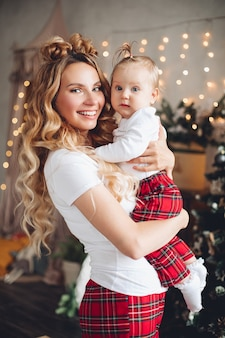 Waist up of happy mother with her cute kid posing on christmas eve
