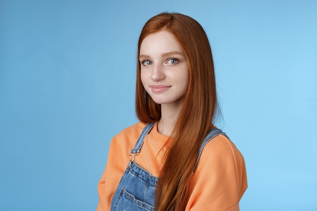 Waist-up kind sincere tender lovely redhead girl wearing orange shirt denim overalls standing half-turned smiling silly gentle grin camera looking friendly pleasantly walk alone blue background.
