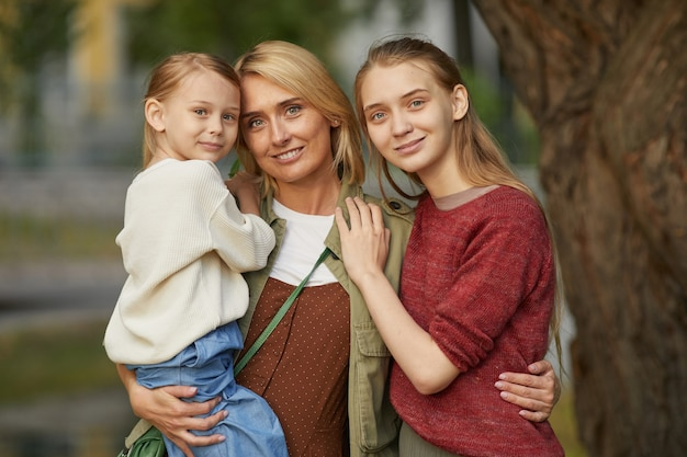 Waist up modern adult mother with two daughters posing together and smiling happily while standing by tree outdoors enjoying family time in park.