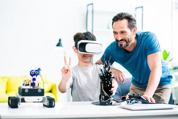 父親が近くに立っている間、ロボット装置を実験している陽気な独創的な少年の腰を上げる