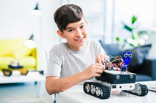 Поднятие талии приятного улыбающегося мальчика, конструирующего современного робота во время подготовки к занятиям