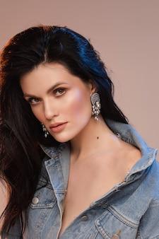 Талия вверх красивой взрослой брюнетки в джинсовой рубашке изолированной на бежевом фоне. концепция красоты