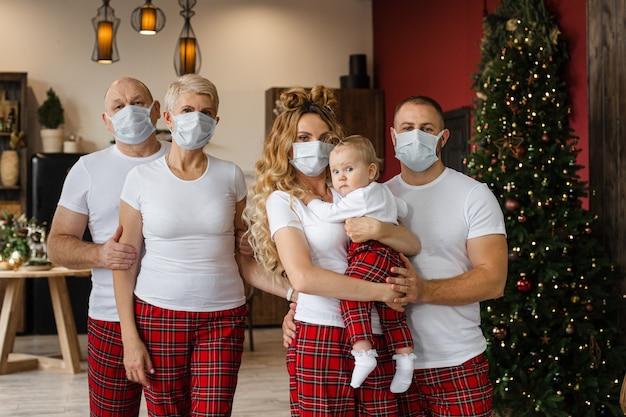 Талия большой семьи в пижаме и защитных масках, стоящая в гостиной в канун рождества