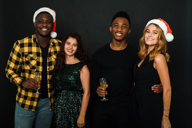 검은 배경에 격리된 새해 파티에서 산타 모자를 쓰고 즐거운 시간을 보내고 샴페인을 마시는 네 친구의 허리까지. 새해나 크리스마스에 건배하는 쾌활한 친구들.