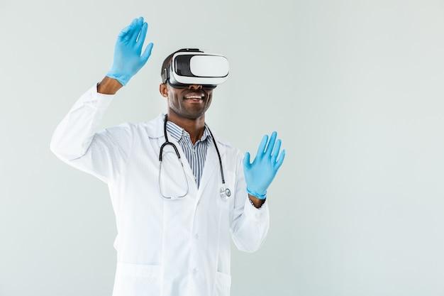 Талия радостного опытного врача в очках vr, стоящего у белой стены