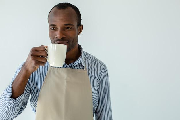 Талия приятного афро-американского официанта, пьющего кофе у белой стены