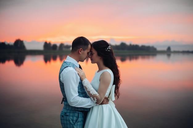 ロマンチックな結婚式のカップルが夕日の湖のそばで抱き締めてポーズをとって、素晴らしい景色を眺めながら腰を下ろします。愛の概念の結婚式のカップル