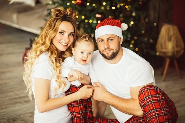 Улыбающаяся пара и милый ребенок сидят на полу с елкой позади талии