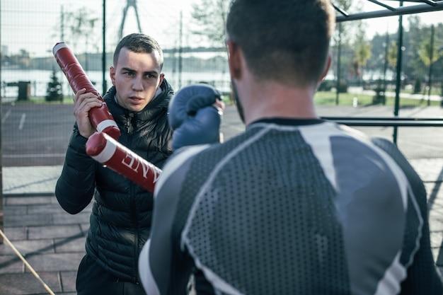 ボクシングのスティックを手に、目の前のスポーツマンを見ながら集中トレーナーを腰に当てる