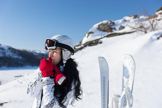 Поднятие талии молодой женщины с длинными темными волосами в лыжных очках и шлеме, стоящей рядом с лыжами и согревающей руки дыханием, глядя вдаль на солнечном снежном склоне горы