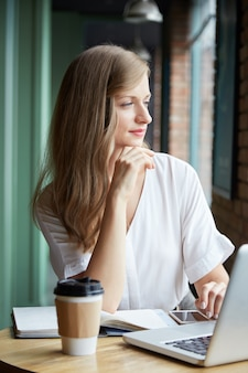 Waist up of pensive young woman sitting at desk looking in the window
