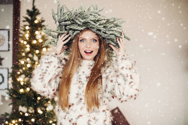 Waist-up photo of excited red-haired lady wearing a crown of fir branches in a swarm of snowflakes