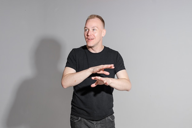 Waist-up photo of expressive man in black shirt crossing his hands while posing at professional studio