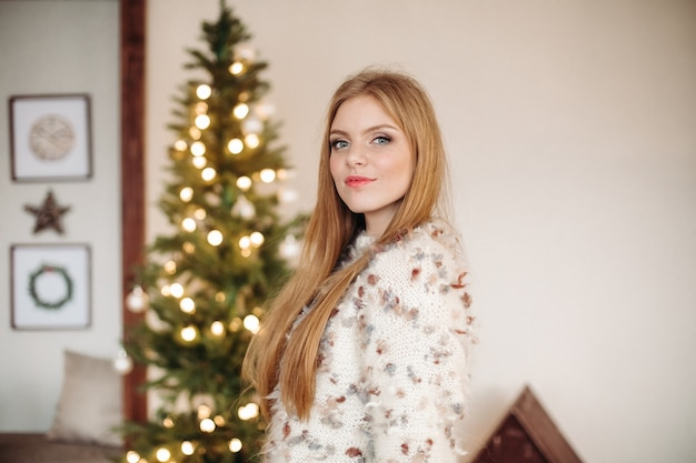 Waist-up photo of a stunning red-haired lady standing near christmas tree