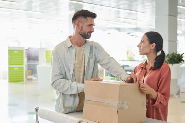 Waist up portrait of adult couple looking at each other while packing cardboard boxes in storage facility or shipping service, copy space