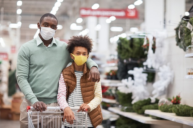 Waist up portrait of african-american family wearing masks in supermarket and looking at camera while posing with shopping cart, copy space