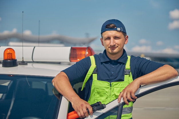 Waist-up portrait of an airport worker with marshalling wands in his hand posing for the camera