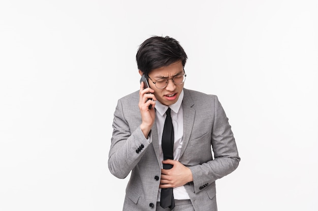Waist-up portrait of asian businessman feeling sick, calling ambulance, bending forward from pain in stomach, suffering stomachache, grimacing as having conversation on phone on white wall