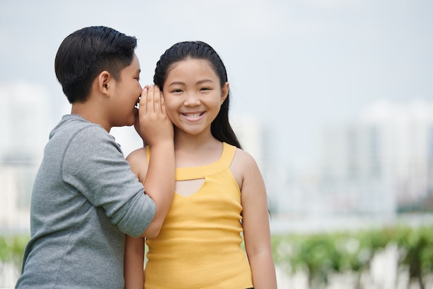 Waist up portrait of asian kids looking at camera, boy whispering a secret to his gorlfriend