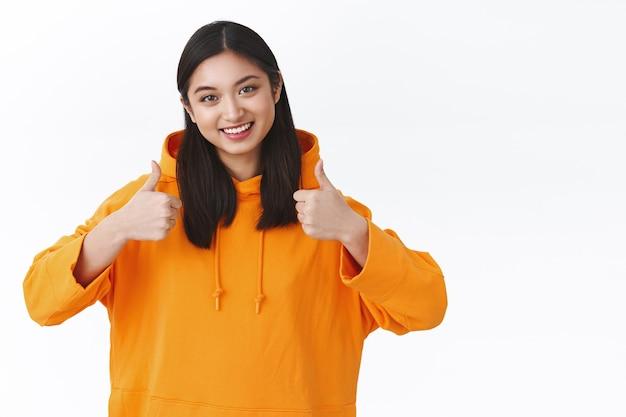 オレンジ色のパーカーを着たウエストアップポートレートアジアのミレニアル世代の女の子は、いいねや承認で親指を立てて、受け入れて笑って、正のフィードバックを与え、良い製品をレビューし、白い壁に立っています