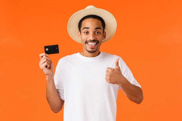 Waist-up portrait attractive smiling african american male tourist using bank service abroad
