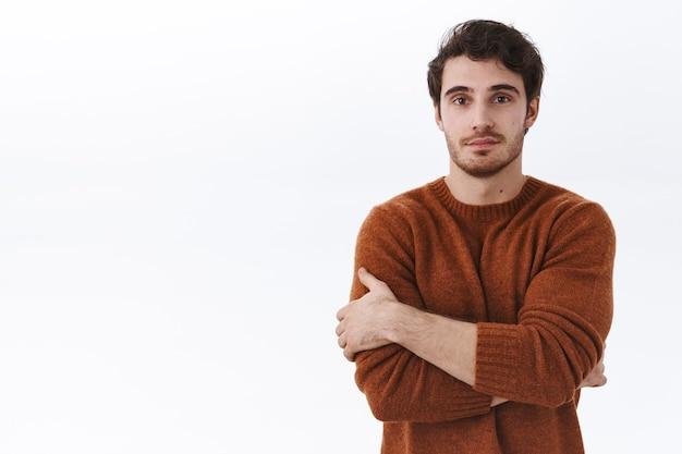 Ritratto in vita di un attraente giovane uomo di 25 anni in felpa marrone