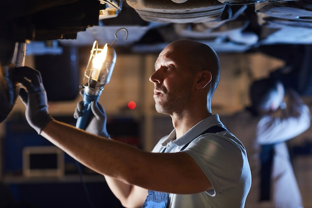 Waist up portrait of bald car mechanic inspecting vehicle while holding flashlight lamp under car lift, copy space