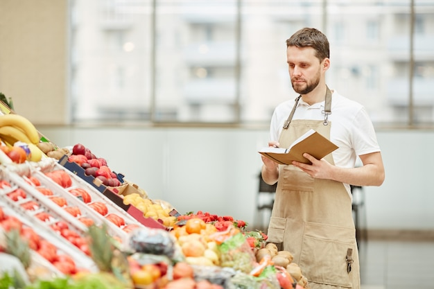 Waist up portrait of bearded man wearing apron standing by fruit and vegetable stand at farmers market while selling fresh produce