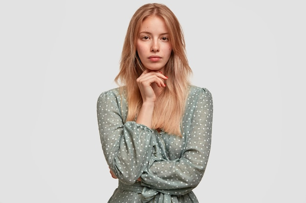 Waist up portrait of beautiful blonde young female with long hair, keeps hand under chin, thinks about something, isolated over white wall. shot of attractive european woman indoor