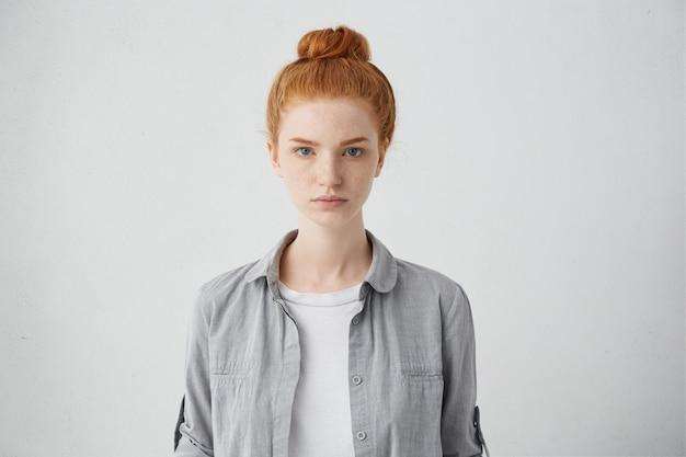 Mezzo busto ritratto di una bella donna europea di 20 anni con le lentiggini e il nodo dei capelli in posa isolata