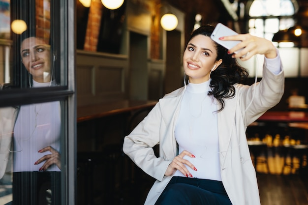 Waist up portrait of beautiful lady with dark hair tied in pony tail wearing white jacket