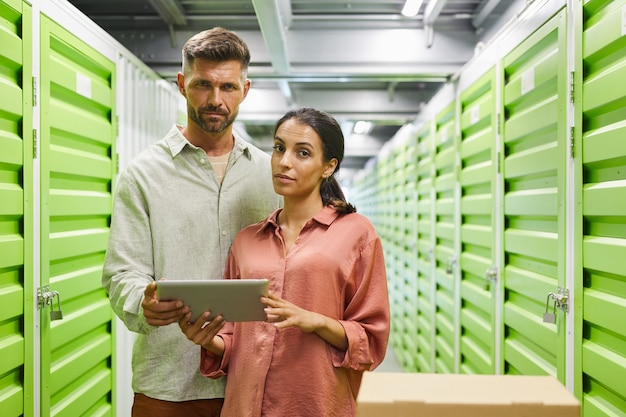 Waist up portrait of beautiful modem couple holding digital tablet while standing by self storage unit and , copy space