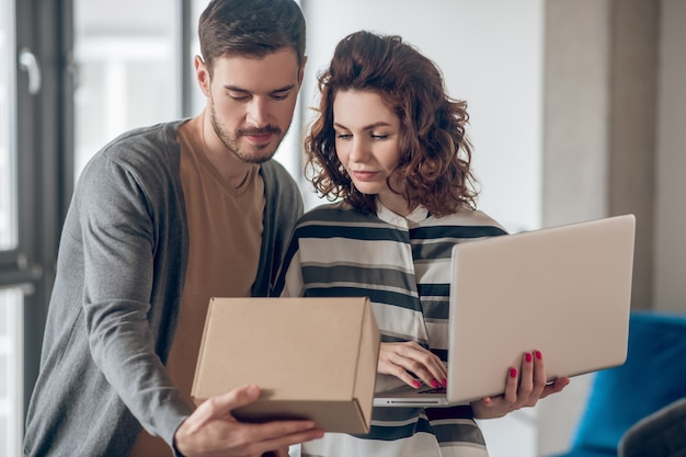 Waist-up portrait of a beautiful woman with a laptop standing by her cute dark-haired male colleague with a cardboard box