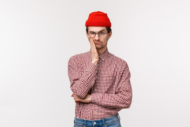 Waist-up portrait bored and unimpressed skeptical young man in red beanie, glasses, facepalm and smirk, grimacing bothered, make annoyed expression as seeing something really stupid