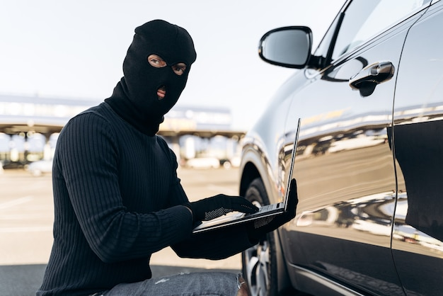 Waist up portrait of the car thief with laptop hacking alarm system while sitting near the car at the daytime. stock photo