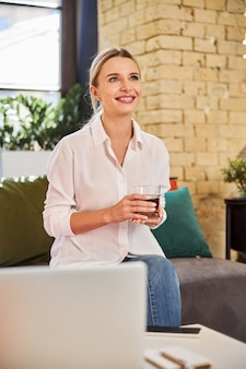 Waist up portrait of charming business lady holding glass with drink in hands while enjoying good time in the beautiful meeting room