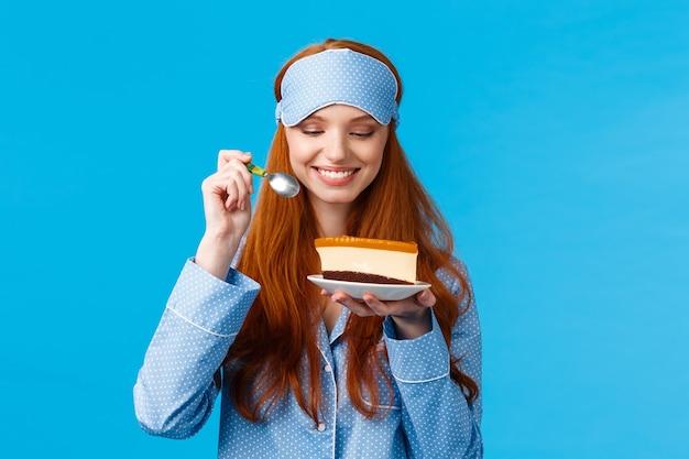 パジャマと睡眠マスクのウエストアップポートレート陽気で喜んで若い白人赤毛の女性