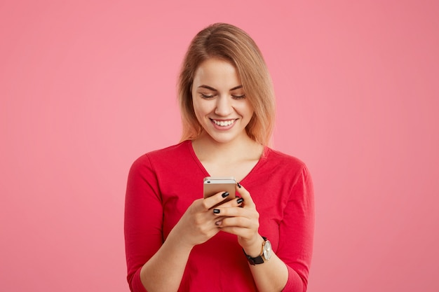Waist up portrait of cheerful female in red sweater uses modern electronic device for online communication, surfes social networks, looks with glad positive expression into screen of cell phone