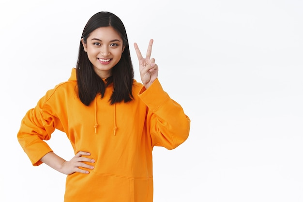カワイイ平和のサインを示し、楽観的な笑顔を見せ、自信を持って行動の準備ができて、あらゆるタスクに取り組み、キャリアの階段を上る、白い壁のウエストアップポートレート陽気な若いアジアの女の子