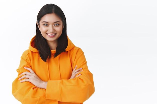 スタイリッシュなオレンジ色のパーカーに腰を下ろした肖像画の自信を持って幸せなアジアの女性、胸の笑顔とカメラを見て、準備と自信を示して、白い壁に立っている