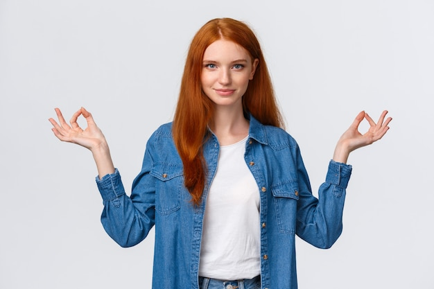 Waist-up portrait confident and relieved, patient good-looking redhead woman calm down daily yoga practice with app, hold hands sideways zen gesture in lotus pose, look assertive