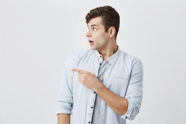 Waist-up portrait of confused caucasian male with bugged eyes gesturing with shocked look at copy space of gray background showing place for your text or promotional information. male advertising