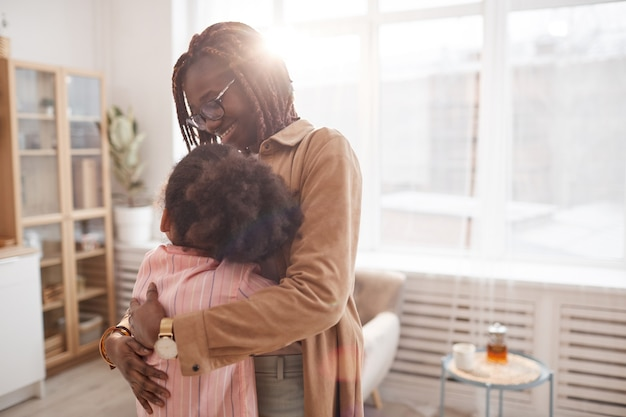 Waist up portrait of contemporary african-american mother embracing daughter while standing in cozy home interior lit by sunlight, copy space