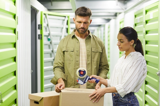 Waist up portrait of contemporary couple packing boxes with tape gun while standing in self storage unit, copy space
