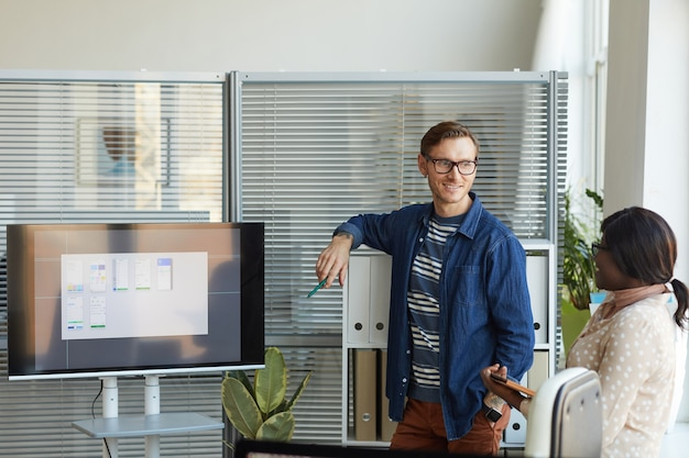 Waist up portrait of contemporary man standing by digital screen while giving presentation at team meeting in it development office, copy space