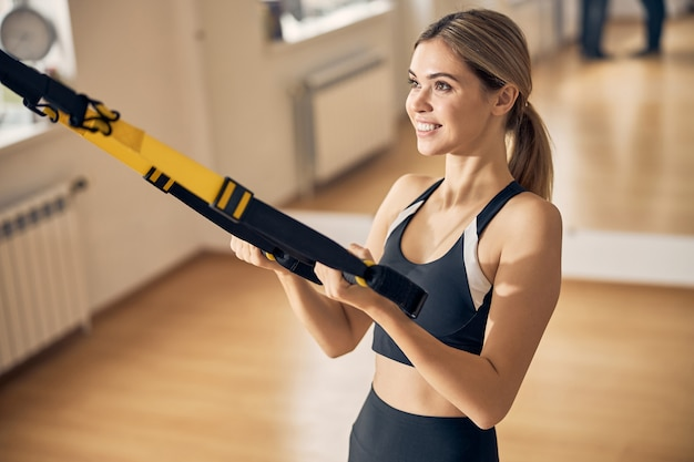 Waist-up portrait of a contented sportswoman strengthening her upper body using suspension trainer