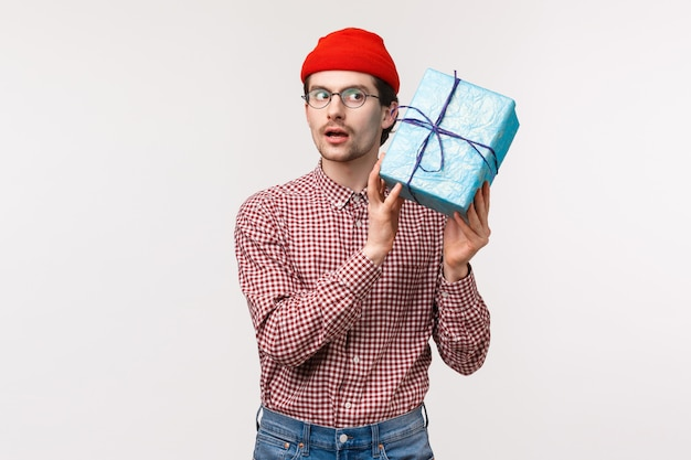 Waist-up portrait of curious funny caucasian bearded man in red beanie, glasses, shaking gift box near ear as trying guess whats inside, look focused, want to open surprise and see present